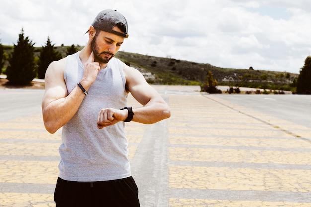 Portrait d'un athlète masculin utilisant une montre intelligente