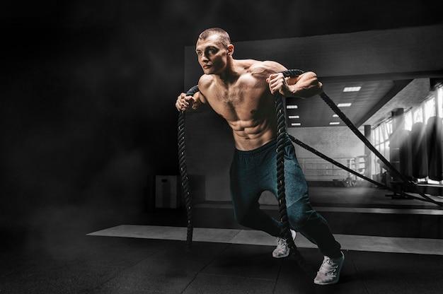Portrait d'un athlète qui tire les cordes. vue d'en bas.