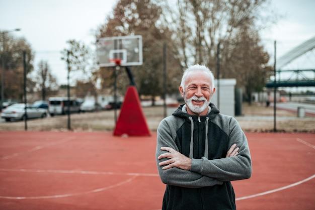 Portrait d'un athlète senior dans un stade en plein air.