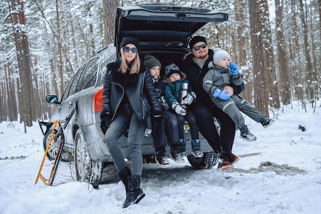 Portrait atmosphérique d'une famille heureuse, ils s'amusent et se détendent pendant leurs vacances dans la forêt d'hiver. père et mère avec leurs enfants sur le coffre de la voiture.