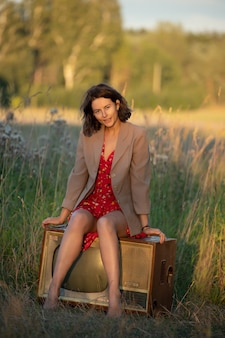 Portrait atmosphérique d'une jeune femme en robe rouge assise sur une vieille télé rétro dans la nature.