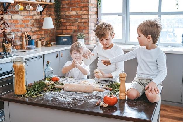 Portrait atmosphérique de trois garçons de famille caucasienne vêtus du même vêtement et souillés de farine dans la cuisine.