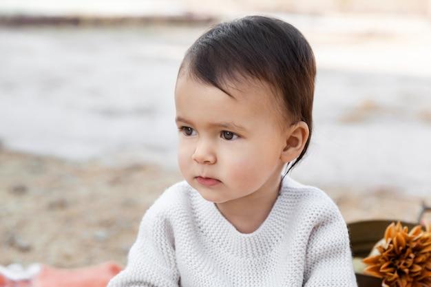 Portrait d'automne de bébé fille assise en plein air portant pull tricoté décontracté