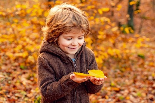 Portrait d'automne d'enfants heureux mignons de petit garçon jouant et rêves dehors en automne