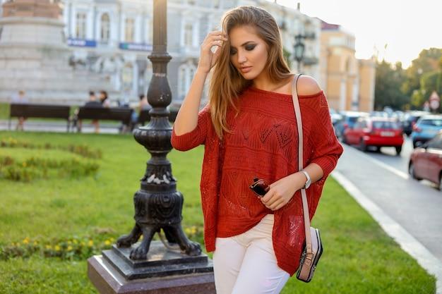 Portrait d'automne d'une jolie blonde blonde avec maquillage lumineux, pull orange et jeans blancs. marcher en plein air.