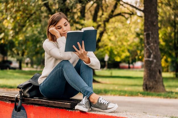 Portrait d'automne d'un livre de lecture belle étudiante heureuse dans le parc.