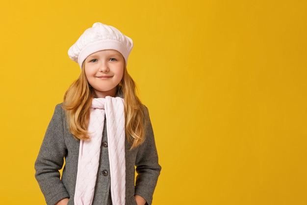 Portrait d'automne d'une petite fille dans un manteau gris et un béret.