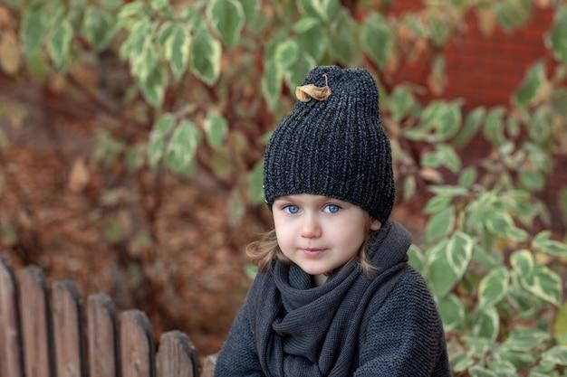 Portrait d'automne d'une petite fille sur fond de feuilles en bonnet et écharpe tricotés chauds gris