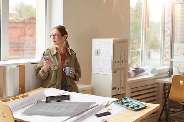 Portrait aux tons chaleureux de jeune femme appréciant le café et regardant la fenêtre pendant la pause-café au bureau,
