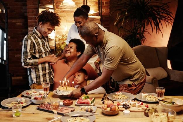 Portrait aux tons chauds d'une famille afro-américaine heureuse célébrant son anniversaire ensemble à l'intérieur le soir