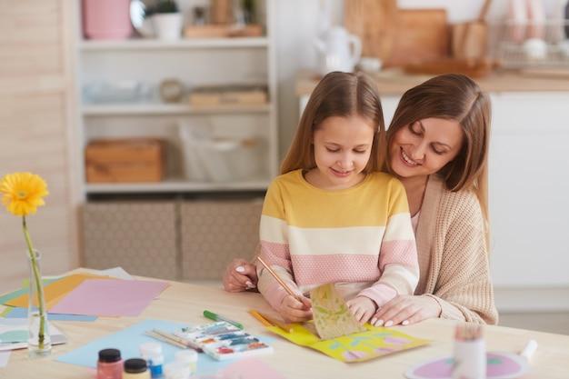 Portrait aux tons chauds de l'heureuse mère étreignant sa fille tout en dessinant des images à la table de cuisine en bois, copiez l'espace