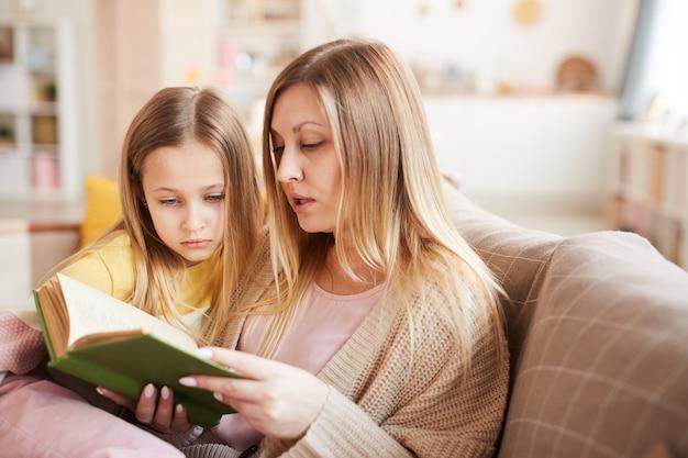 Portrait aux tons chauds de livre de lecture de mère mature à petite fille assise sur un canapé dans un intérieur confortable