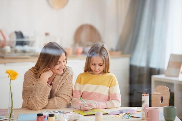 Portrait aux tons chauds de mère mature aidant sa fille mignonne avec un projet d'art et d'artisanat à l'intérieur de la maison, copiez l'espace