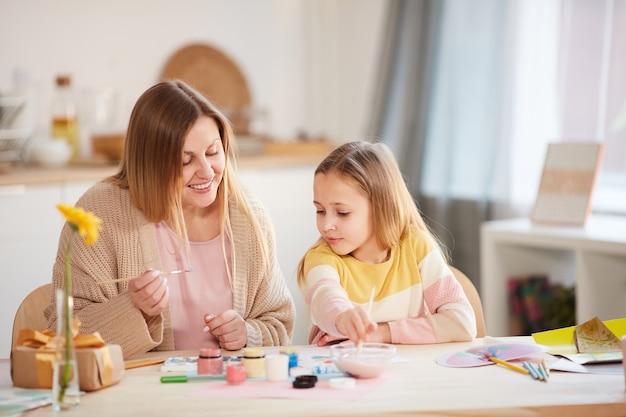 Portrait aux tons chauds de la mère mature souriante peinture photos avec mignonne petite fille alors qu'il était assis à une table en bois dans un intérieur confortable