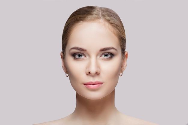 Portrait avant de la belle jeune femme blonde aux yeux verts sur fond gris agrandi. fille avec une peau propre