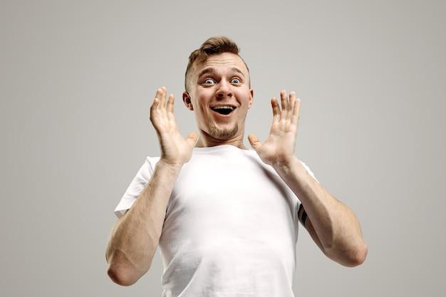 Portrait avant demi-longueur mâle attrayant sur fond de studio gris. jeune homme barbu surpris émotionnel debout avec la bouche ouverte. émotions humaines, concept d'expression faciale