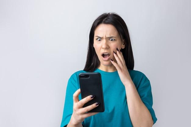 Portrait avant d'une jeune femme souriante utilisant un téléphone portable sur fond gris