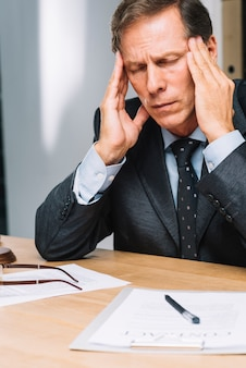 Portrait d'un avocat mature stressé touchant sa tête au bureau
