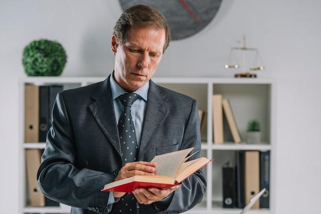 Portrait d'un avocat mûr lisant un livre dans la salle d'audience