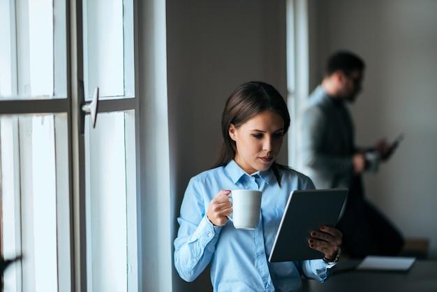 Portrait d'une avocate en train de regarder des documents, tenant une tasse.