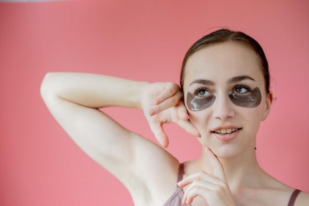 Portrait de balle dans la tête bouchent souriante jeune femme avec masque de patchs hydratants sous les yeux regardant la caméra en appréciant la procédure de soin de la peau.