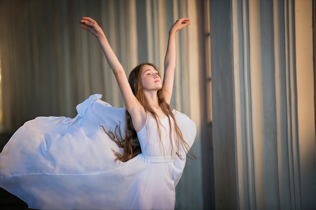 Portrait d'une ballerine aux cheveux longs lâches dans une jupe blanche qui coule comme du lait