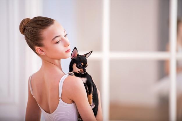 Portrait d'une ballerine en blanc avec un petit chien chihuahua dans ses mains dans une belle salle blanche devant un miroir.