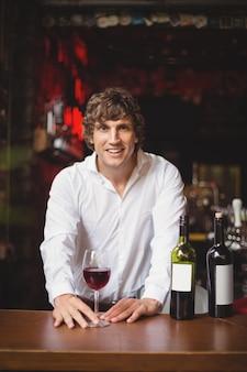 Portrait de bar tendre avec verre de vin rouge