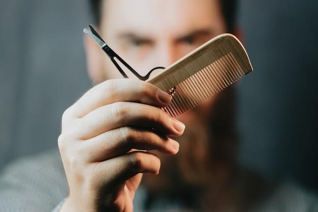 Portrait de barbu tenant des équipements à la main, regardant la caméra, isolé sur fond pastel