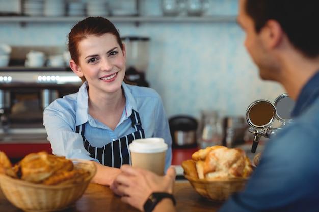 Portrait de barista heureux donnant du café au client au café