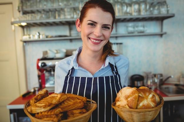 Portrait de barista heureux offrant des pains au café