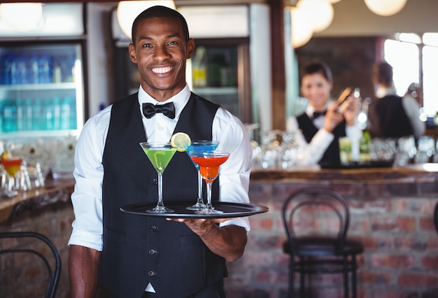 Portrait de barman tenant un plateau de service avec des verres à cocktail