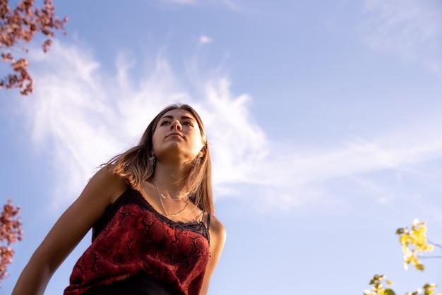 Portrait d'en bas d'une jeune adolescente blonde. fond de ciel bleu.