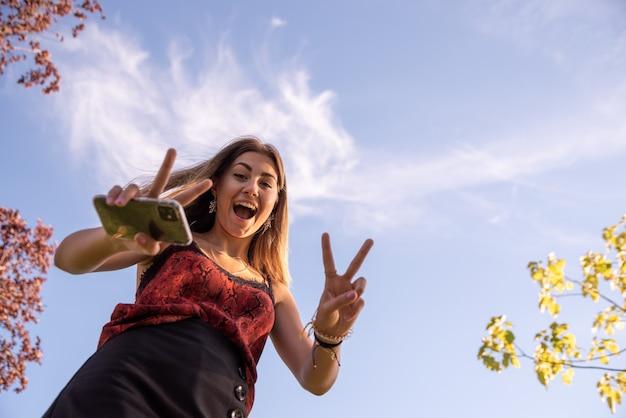 Portrait d'en bas de la jeune adolescente blonde heureuse regardant la caméra. fond de ciel bleu.
