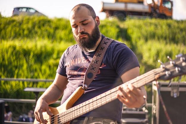 Portrait d'un bassiste barbu lors d'un concert live au coucher du soleil #2