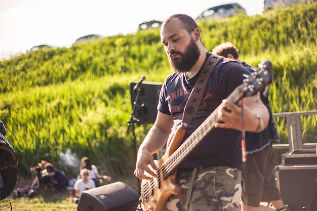 Portrait d'un bassiste barbu lors d'un concert live au coucher du soleil