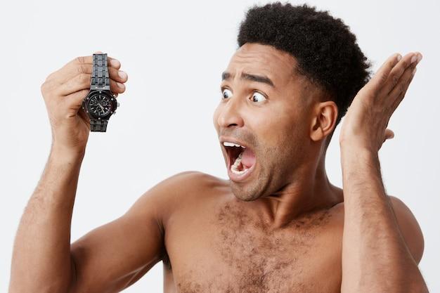 Portrait de beau beau mâle afro-américain aux cheveux bouclés sans vêtements tenant la montre à la main dans les mains, regardant avec une expression stressée et confuse, criant fort