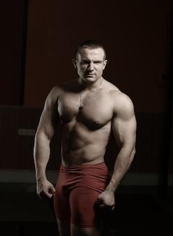 Portrait de beau bodybuilder mâle isolé sur fond noir