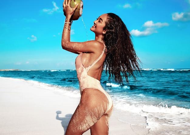 Portrait, de, beau, caucasien, bains de soleil, modèle femme, à, longs cheveux noirs, dans, maillot de bain beige, poser, sur, plage été, à, sable blanc, sur, ciel bleu, et, océan