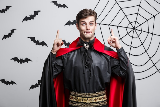 Portrait de beau caucasien en costume d'halloween vampire pointant sur le côté.