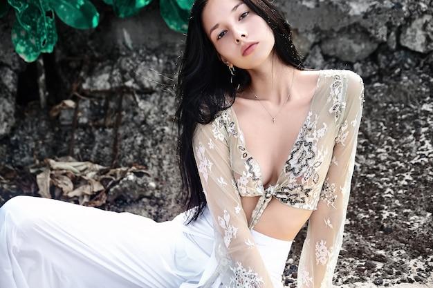 Portrait, de, beau, caucasien, femme, modèle, à, sombre, cheveux longs, dans, large-leg, pantalon classique, poser, près, rochers, et, vert, exotique, tropical, feuilles, fond