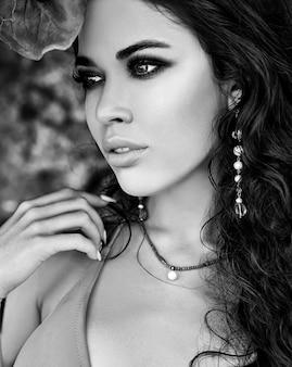 Portrait, de, beau, caucasien, femme, modèle, à, sombre, cheveux longs, dans, rose, maillot de bain, poser, sur, près, vert, feuille tropicale