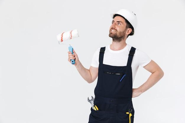 Portrait d'un beau constructeur barbu portant une salopette debout isolé sur un mur blanc, tenant un pinceau