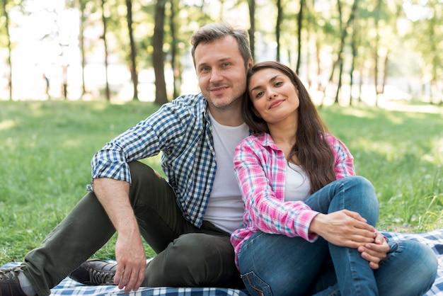 Portrait de beau couple d'amoureux assis dans le parc