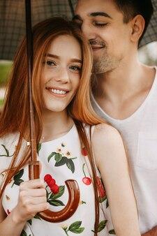 Portrait d'un beau couple assis sous le parapluie tandis que l'homme touche ses cheveux de petite amie avec son visage alors qu'elle regarde la caméra en souriant.