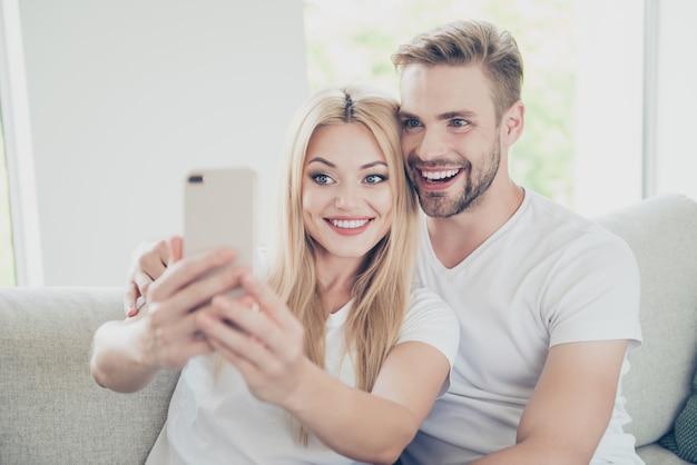 Portrait de beau couple branché à la maison assis sur le divan faisant selfie
