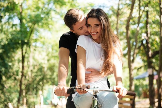 Portrait d'un beau couple à cheval sur un vélo ensemble