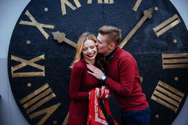 Portrait de beau couple élégant debout près de l'horloge.