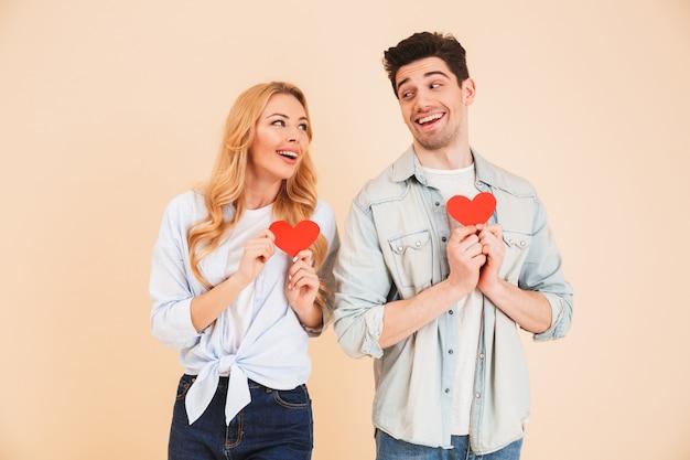 Portrait de beau couple homme et femme en vêtements de base se regardant avec sourire et tenant deux coeurs de papier rouge, isolés sur mur beige