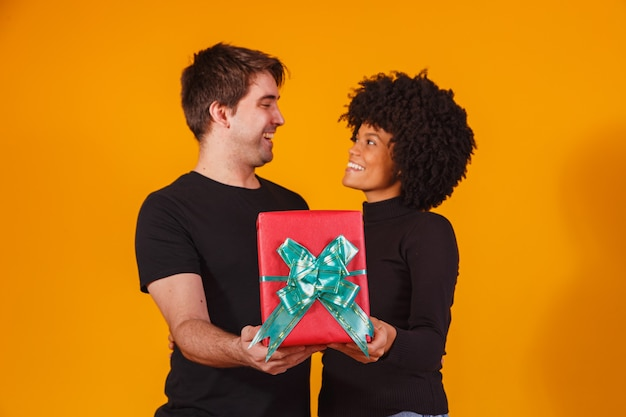 Portrait d'un beau couple sur jaune avec un cadeau